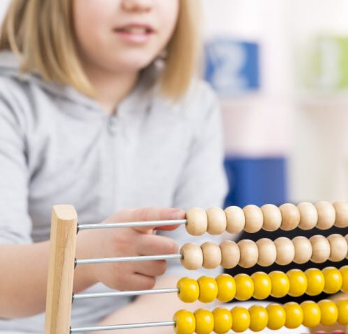 Little blond girl using abacus to learn how to count